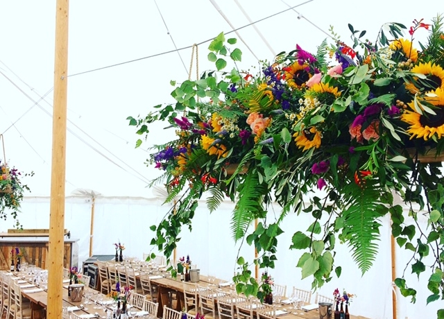 Marquee ceiling decorations, hanging floral arrangement, floral swing, sunflowers, foliage, vibrant, tropical