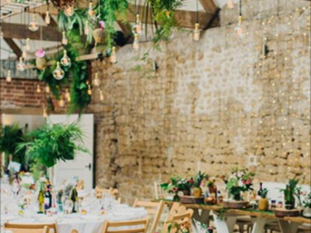 Tropical flower and foliage barn wedding with hanging foliage garlands and pineapples