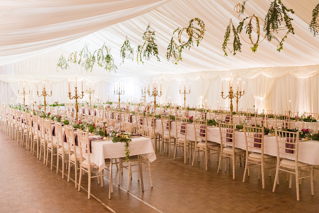 Banquet style foliage tablescape with tea lights, candelabras, foliage garland table runner, jewelled flowers, hanging gold terrarium with trailing foliage