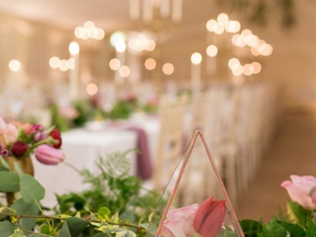 Gold terrarium with red tulip and lilac rose, textured foliage table runner, foliage garland, candle light, banquet style tables