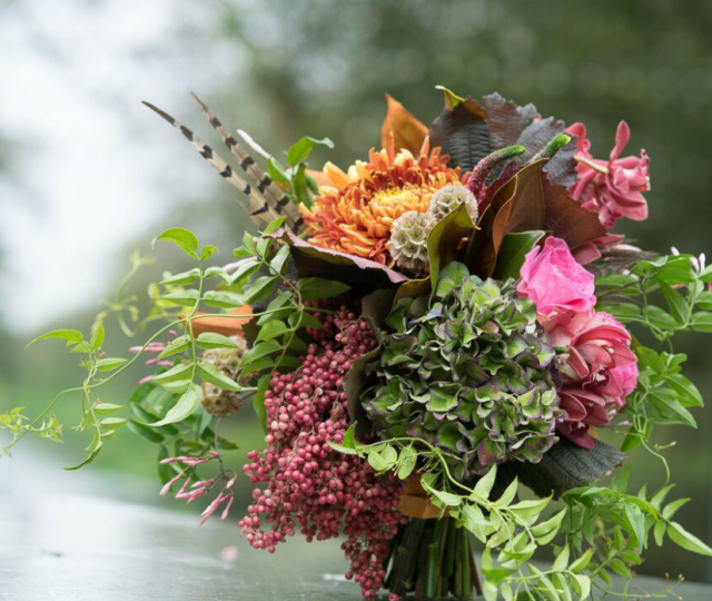 Textured autumnal bridal bouquet hydrangea peacock feathers orchid rose