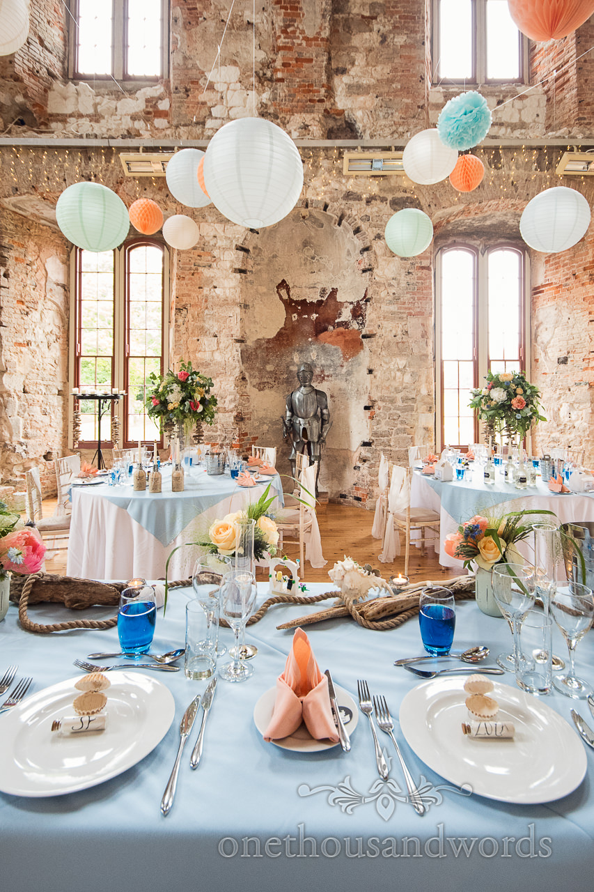 lulworth-castle-wedding-breakfast-room-with-oranges-and-blues-and-chinese-lanterns- luxury-table-centrepiece