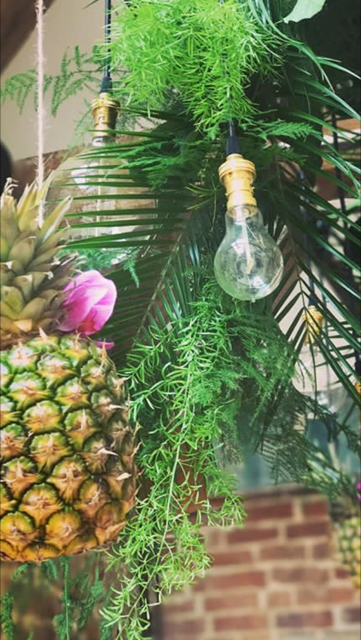 Pineapple and Edison bulb ladder installation with textured foliage garland