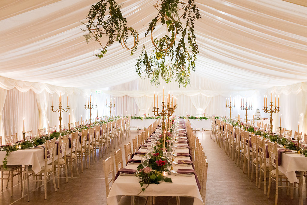 Hanging gold terrarium with textured foliage, banquet style table centrepiece with foliage garland, gold candelabras and jeweled coloured flowers