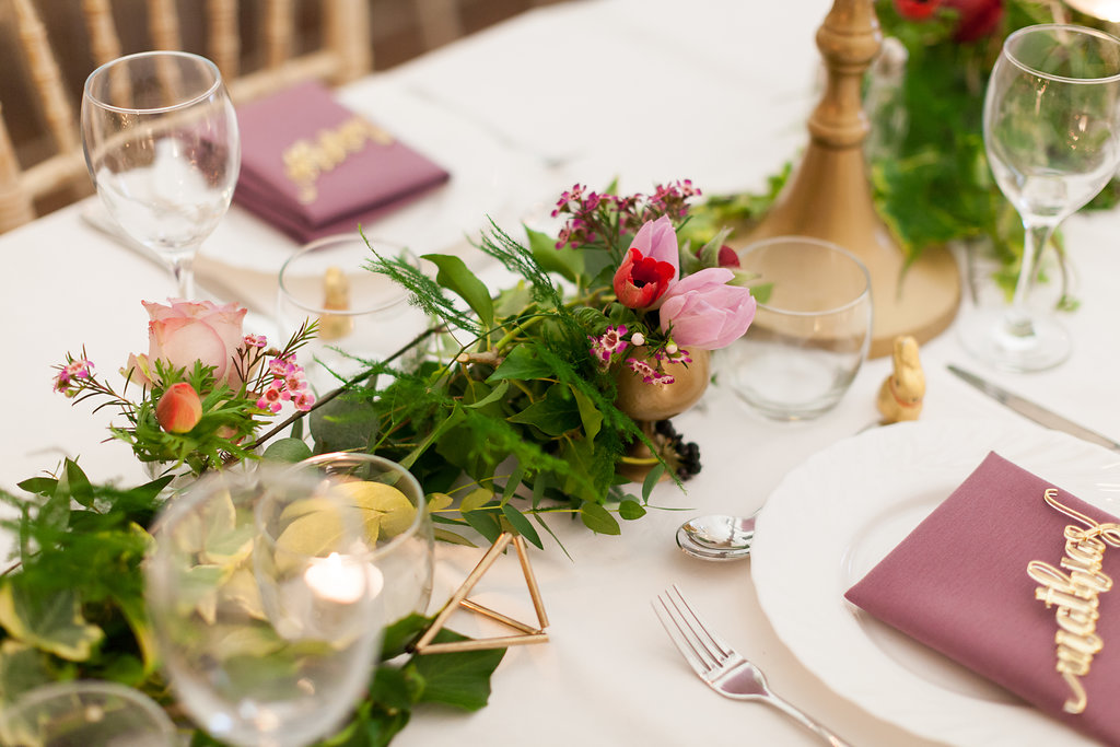 Foliage tablescape with mini gold jars of flowers, gold terrarium, tulips, candlestick