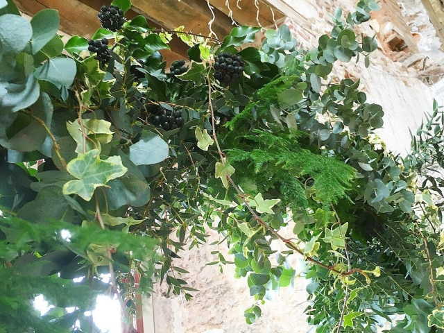 textured foliage moon gate, lulworth castle, dorset, ceremony, wedding arch, wedding flowers. ivy, fern, woodland, eucalyptus