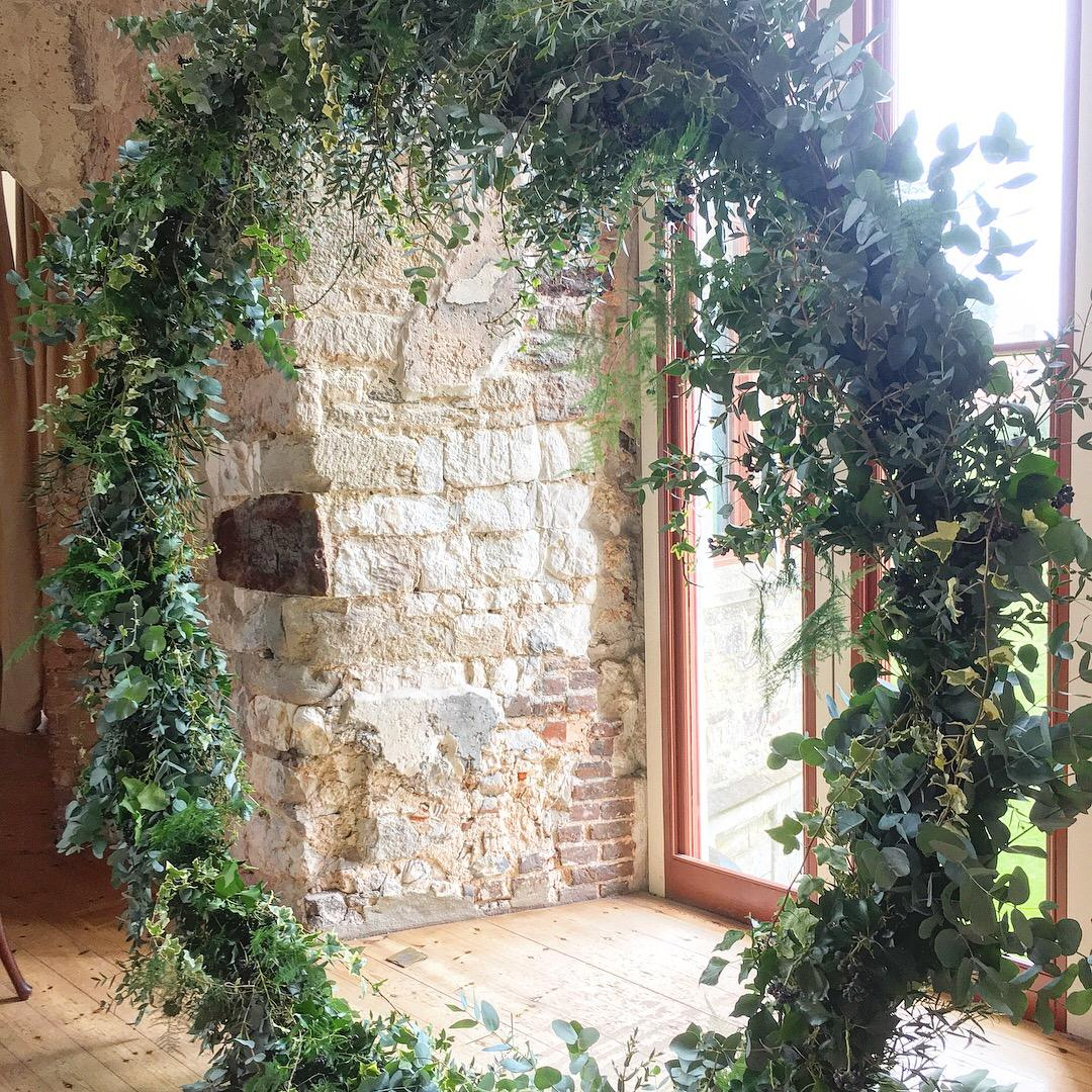 textured foliage moon gate, lulworth castle, dorset, ceremony, wedding arch, wedding flowers, rustic