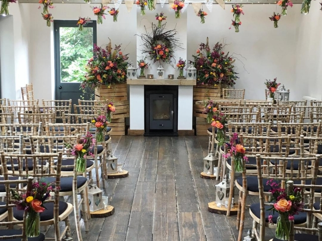 Rustic. wild. garden flower, vibrant, coral, yellow, jam jar, hanging flowers, beam installation, wedding ceremony flowers
