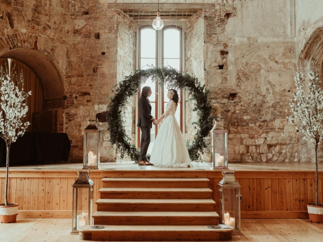 textured foliage moon gate, lulworth castle, dorset, ceremony, wedding arch, wedding flowers