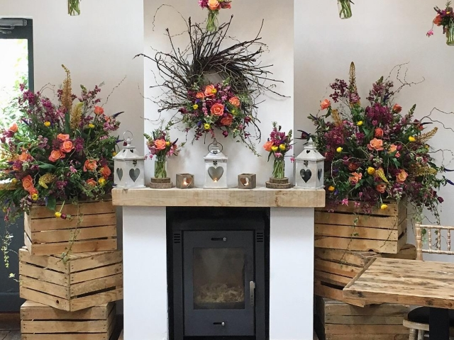 Fireplace, rustic. wild. garden flower, vibrant, coral, yellow, jam jar, hanging flowers, beam installation, wedding ceremony flowers