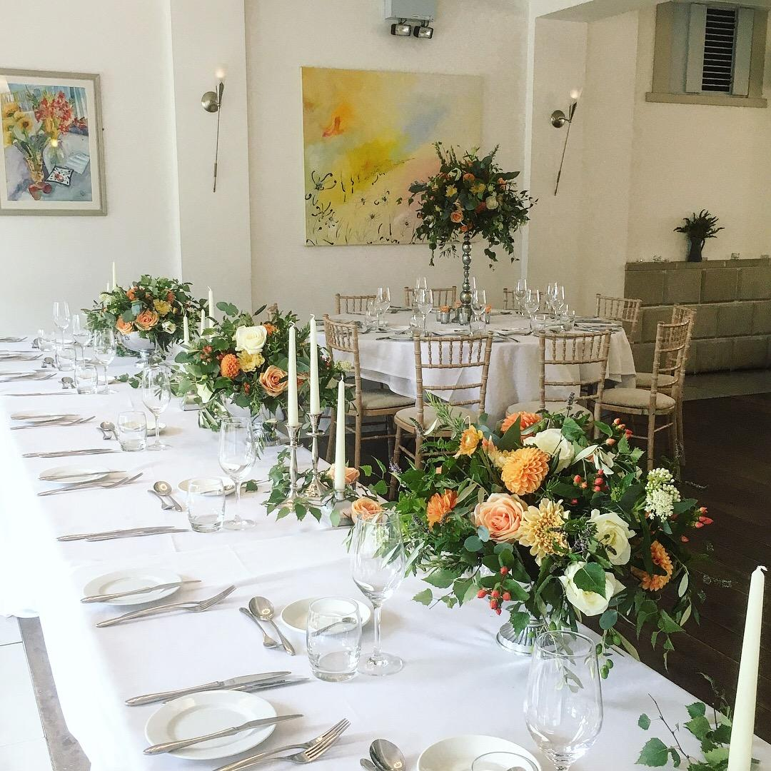 Top table tablescape, silver urn table centrepiece, orange, peach flowers, silver candlestick, Italian villa wedding flowers