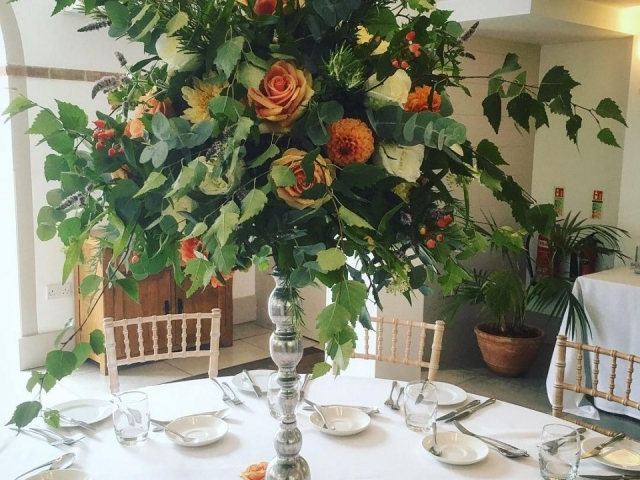 WILD TEXTURED FOLIAGE ORANGE PEACH SUMMER FLOWERS TALL TABLE CENTREPIECE SILVER CANDLESTICK ARRANGEMENT