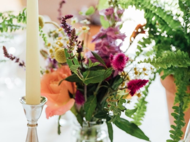 Fern and succulent plant tablescape, floral jam jar, vibrant flowers, garden flowers, table centrepiece, silver candlestick, tea lights, new forest wedding. wedding florist, wedding flowers
