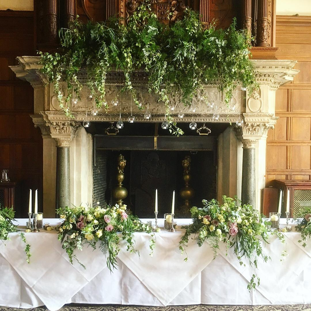 Top table flowers, tablecentrepiece, foliage tablerunner, Foliage fireplace arrangement, hanging tea lights, tablescape, woodland wedding, rhinefiled, lilac. lavender, foliage, silver candlestick, tealights