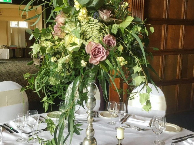 Lilac rose, snow berry, dried lavender, Tall silver candlestick table centrepiece, wild foliage arrangement, woodland wedding, wedding flowers, rustic wedding flowers, rhinefiled wedding, Dorset