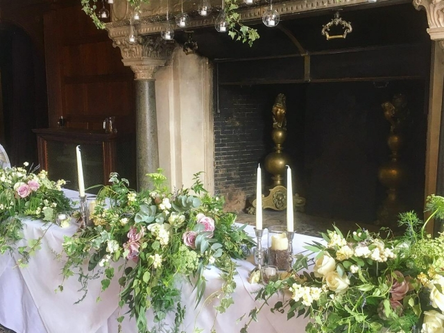 Top table flowers, tablecentrepiece, foliage tablerunner, tablescape, woodland wedding, rhinefiled, lilac. lavender, foliage, silver candlestick, tealights