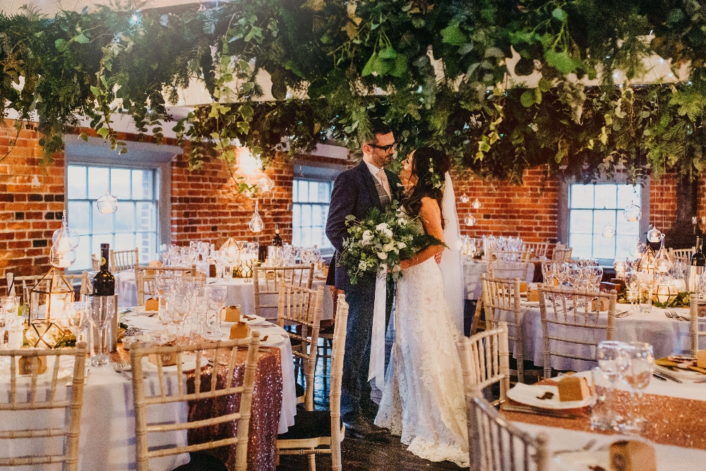 sopley mill winter wedding, foliage beam decoration, hanging tea lights, cosy wedding flowers