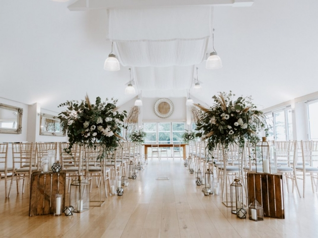 woodland ceremony styling, large rustic foliage arrangement,gold metal stands, candle light, willow trees wrapped in copper wire fairy lights, wedding florist, flowers, Dorset, Hampsh