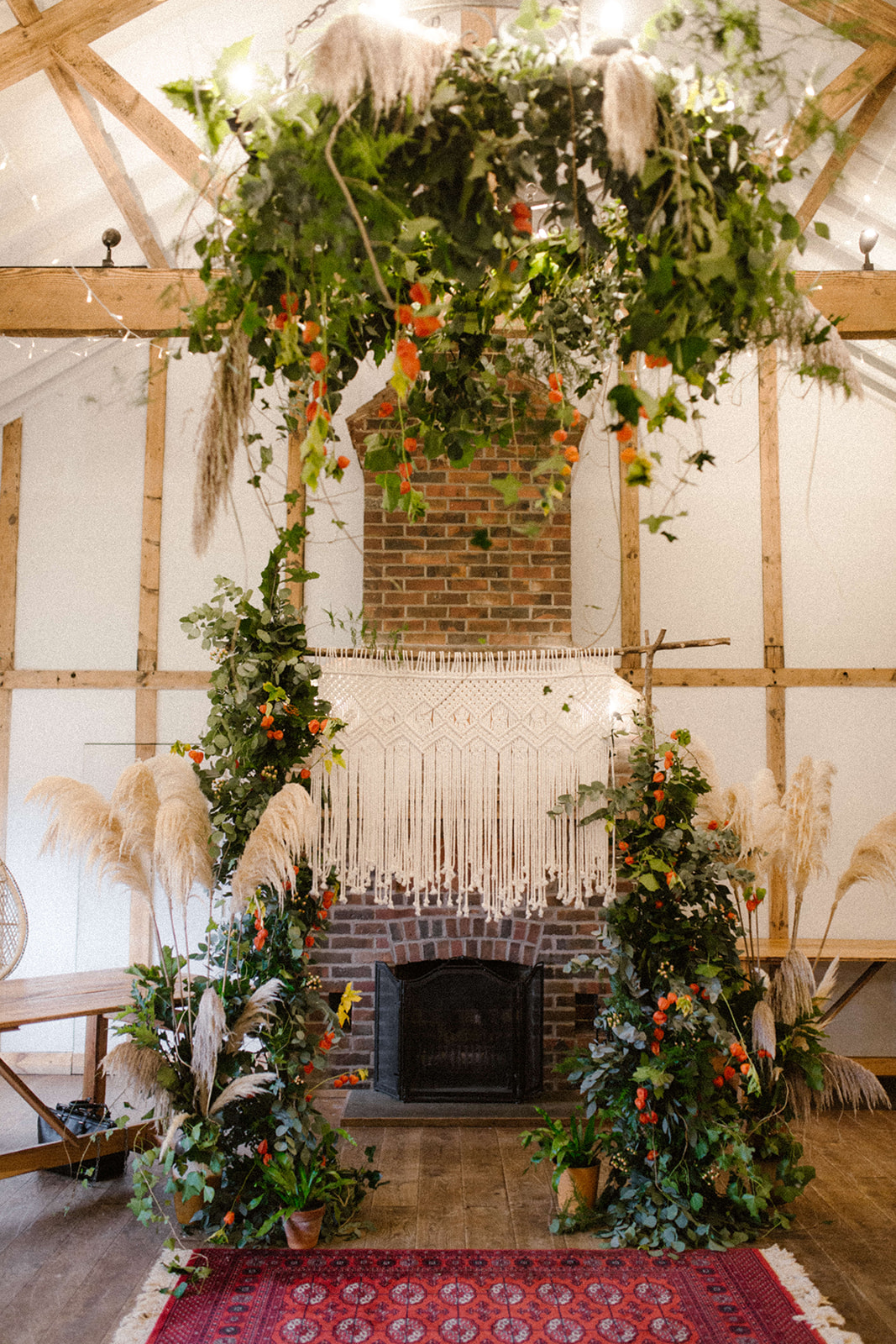 Hanging foliage chandelier, boho ceremony, macrame arch, pampas grass, boho rugs, woodland wedding, ferns, plants wedding dorset hampshire new forest burley manor